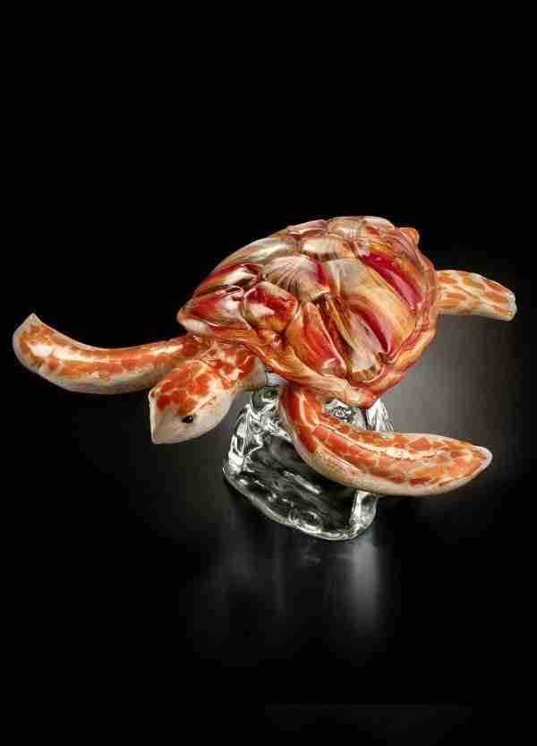 Gorgeous handmade Murano glass sculpture of a colored turtle resting on a blown base in crystal color.