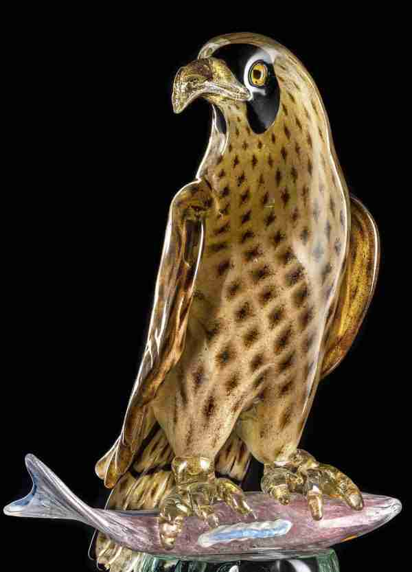 Hawk during a hunting trip resting on a pole with the captured prey, a beautiful fish, entirely handmade in glass.