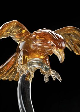 Amber colored falcon made of Murano glass by hand by our glass masters, the falcon is supported by a transparent glass base.