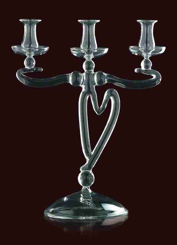 Candlestick with heart, with three flames, in Murano glass. The color of the candlestick is in transparent crystal. Warranty certificate.